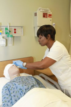 Practical Nursing student works on mannequin - Exam Room Procedures - Nurse Aide - Medical Assisting - Basic Certificate (C45400A)Medical Assisting - Basic Certificate (C45400A) - Practical Nursing Diploma (D45660)